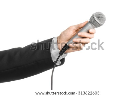 Business and speech topic: Man in black suit holding a gray microphone on an isolated white background in studio