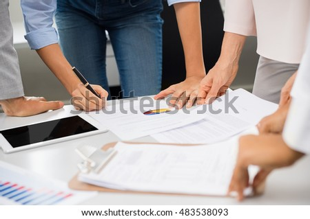 Business charts and graphs showing the results of the successful teamwork. Close up hands of businessmen and businesswomen analyzing financial reports. Businesswoman signing contract.