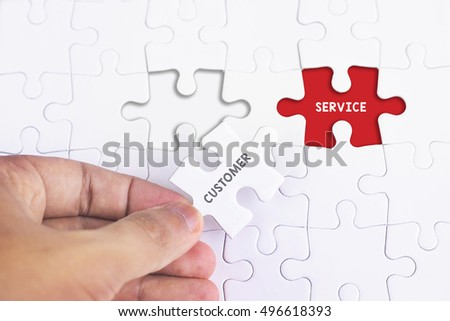 Business Concept - Female hand and missing puzzle with CUSTOMER AND SERVICE  WORD