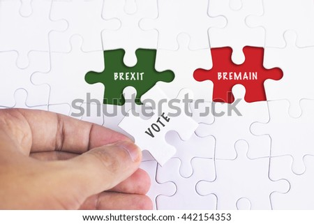Business Concept - Female hand and missing puzzle with VOTE BREXIT BREMAIN
