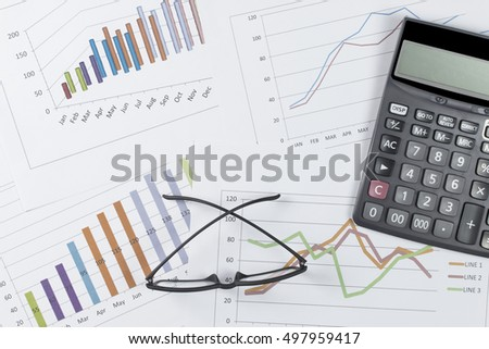 business concept : graph with glasses and calculator on stock market report as background