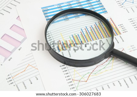 Business concept, magnifying glass on financial charts and graphs
