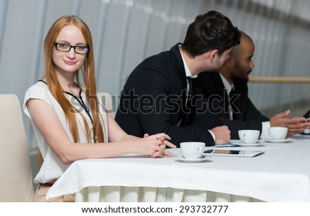 Business confidence. Portrait of young motivated successful businesswoman at work. Her business partners are working on the background.