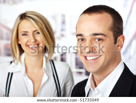 Business couple smiling looking at camera male on focus