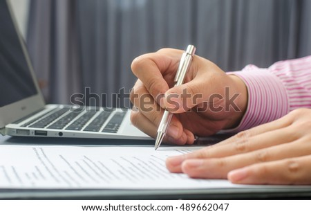 business, education, people and technology concept - close up of male hands with laptop computer, notebook and pen taking notes