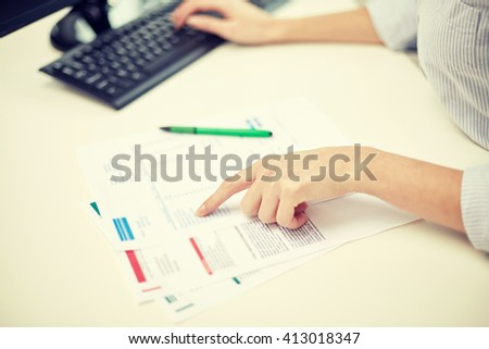 business, education, people and technology concept - close up of woman hands with papers and computer in office