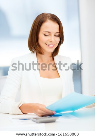 business, education, school, documents, people concept - businesswoman or student working with graphs in office
