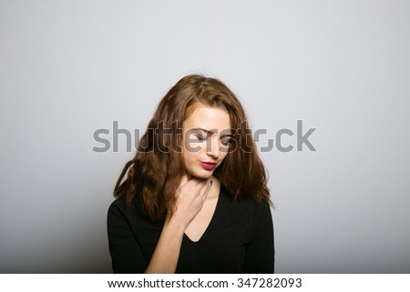 Business lady slim has a sore throat, studio shot isolated on the gray background