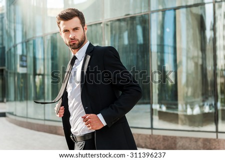 Business leader. Confident young businessman adjusting his jacket and looking at camera while standing outdoors with office building in the background