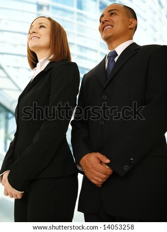 business man and business woman standing and looking up smiling. concept for successful team work