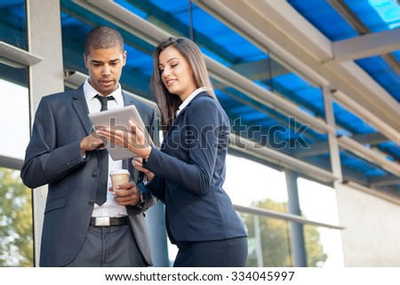 Business man and woman with tablet computer ,talking