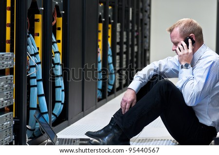 business man calling on a smartphone and looking at a laptop computer in a network data center
