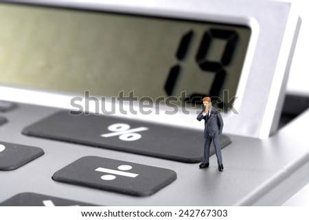 Business man figurine standing on calculator