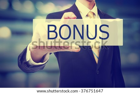 Business man holding Bonus on blurred abstract background