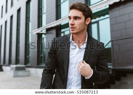 Business man in suit outdoors looking aside