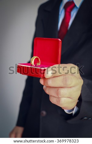 Business man in suit showing ring in ring box