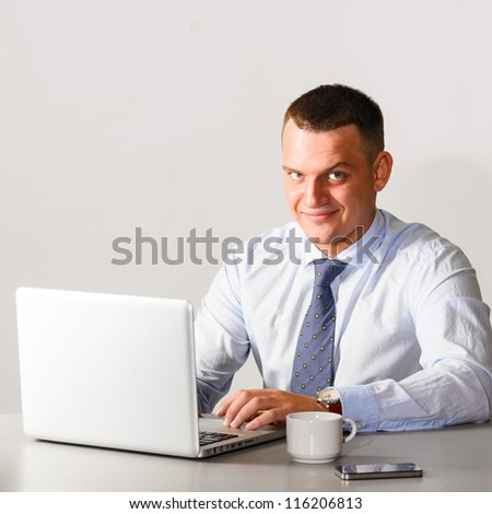 business man is sitting at his table with laptop