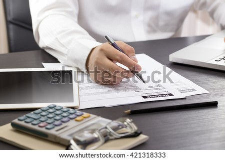Business man review his resume on his desk, digital tablet, calculator, eyeglass and cup of coffee