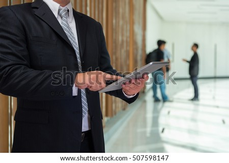 business man touch on smart phone or tablet with blurred business people talking background
