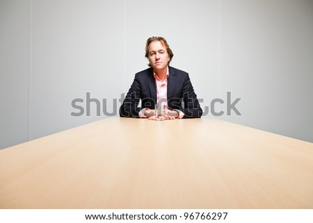Business man with blond hair sitting bored behind table with glass of water in office isolated on white background