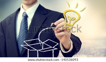 Business man with Idea light bulb coming 'out of the box' with a big city backdrop