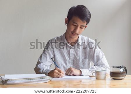 business man working and writing with paper sheet at work table