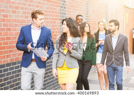 Business multiracial group walking in London. They all are young, smiling and wearing smart casual clothes. Mixed race group. Teamwork and business concepts.