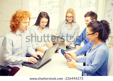 business, office and startup concept - smiling creative team with table pc and laptop computers working in office