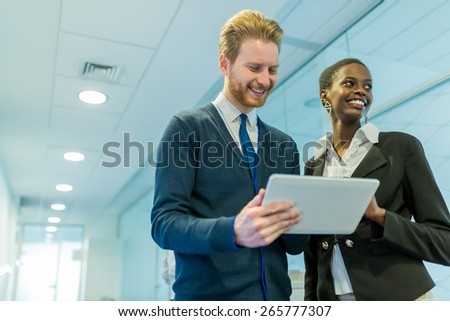 Business partners and colleagues discussing ideas displayed on a tablet on an office corridor