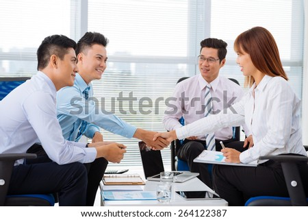 Business partners shaking hands at the meeting