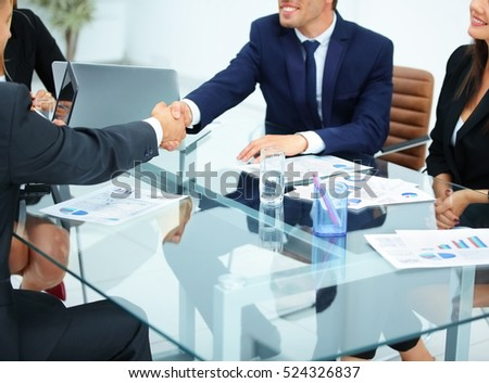 business partners sitting at a table in the office and shake hands. in the workplace are financial charts and laptops are ready to work