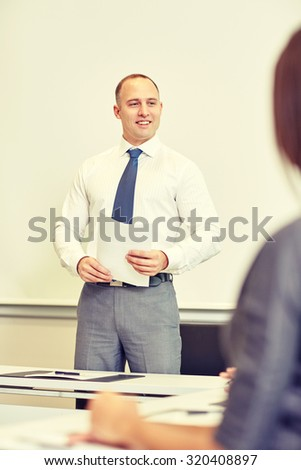 business, people and planning concept - smiling businessman and woman with papers meeting on presentation in office