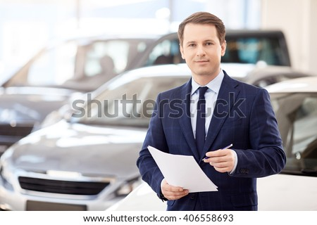 business, people, car sale and technology concept - happy smiling businessman in suit holding documents over auto show or salon background
