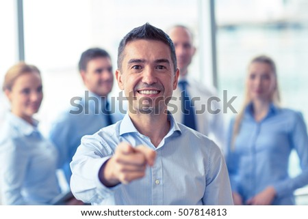 business, people, gesture and teamwork concept - smiling businessman pointing finger to you with group of businesspeople meeting in office