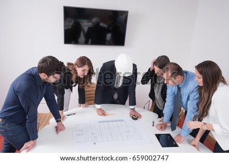 Business people group on meeting construction stock photo business people group on meeting with construction engineer architect looking building blueprint in modern office malvernweather Gallery