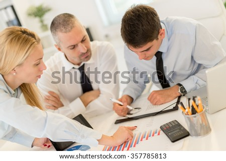 Business people having a meeting. Three business people looking at document and discussing in the office.