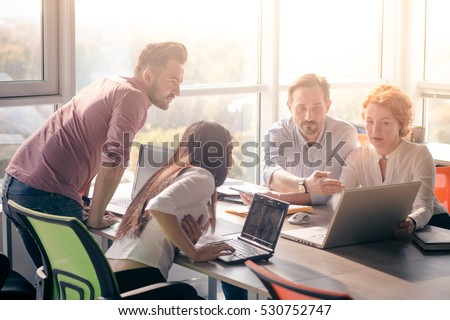 Business people looking at laptop computer and discussing photo of diagram, scheme in board room in office. Business meeting concept.