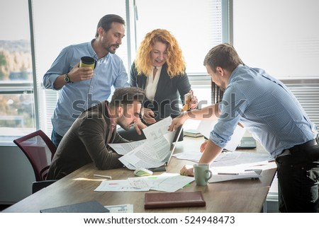Business people looking through documents all together and happy smiling while working in team in board room in office interior. Teamwork concept.