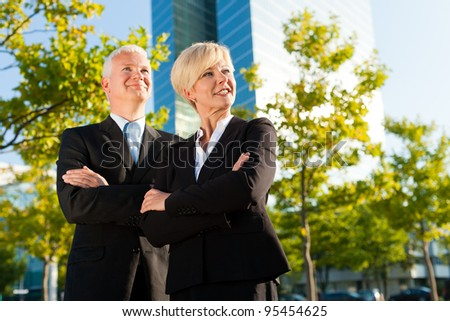 Business people - mature or senior - standing in a park outdoors in front of a office building
