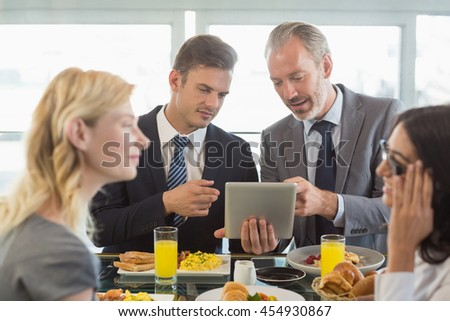 Business people using digital tablet while having meal in restaurant