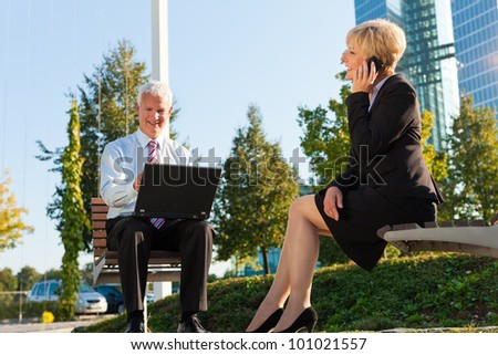 Business people working outdoors - he is working with laptop, she is calling someone