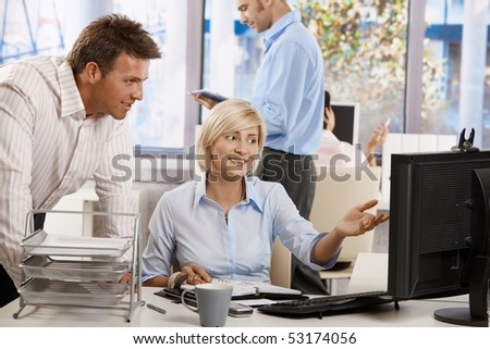 Business people working together in office, using persnal organizer and desktop computer.