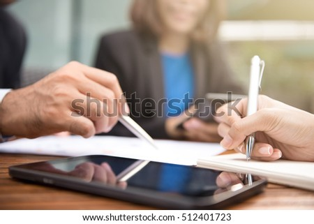 Business people writing and discussing documents with tablet computer on the table