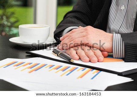 Business person with hands crossed analyzing a bar charts