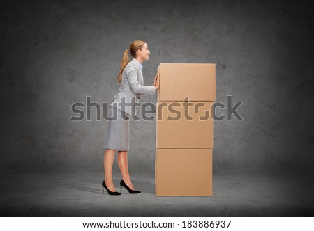 business, post and transportation concept - smiling businesswoman pushing tower of cardboards