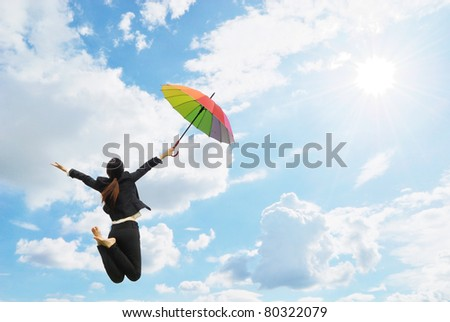 Business rainbow umbrella woman jumping to blue sky