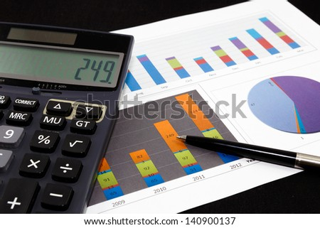 Business report  graph with pen and calculator