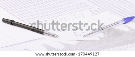 Business still-life of a pen, charts, tic tac toe