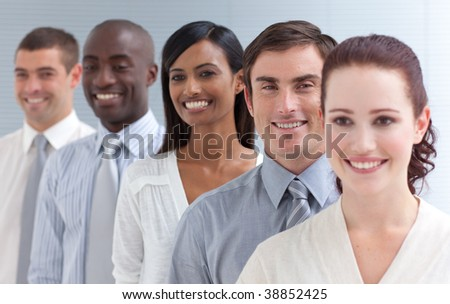 Business team in a line smiling at the camera. Focus on an attractive man