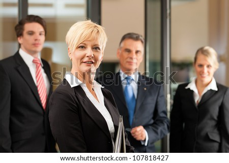 Business - team in an office, the female manager is standing in front